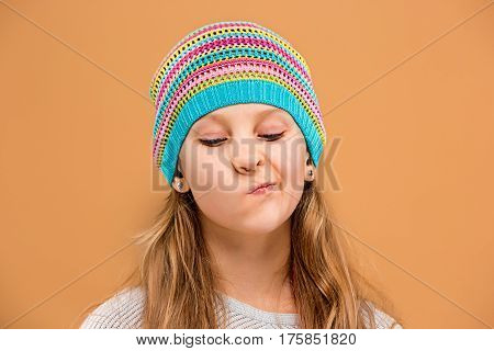 The face of unhappy sad teen girl in hat on brown studio background