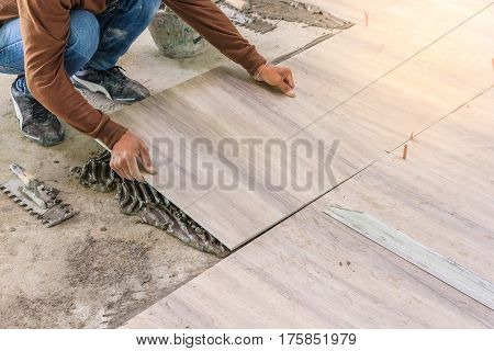 Home improvement renovation - construction worker tiler is tiling ceramic tile floor adhesive