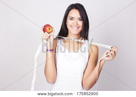 Young Caucasian Woman Holding A Measure Tape And Apple
