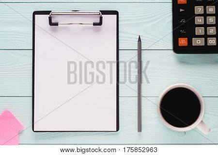 Folder clipboard with white blank paper sheet pencil cup of coffee and calculator with copy space top view. Business concept. Blank clipboard on wooden background flat lay.