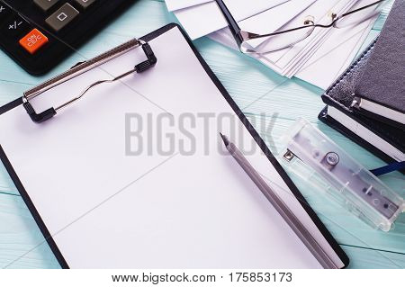 Business objects (black clipboard with blank sheet of paper pencil glasses envelopes and calculator) top view. Space for text. Workplace with office supplies. Copy space.