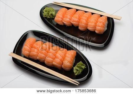 Salmon sushi, wooden sticks and sauce of wasabi on two black ceramic plates of a bean-shaped form