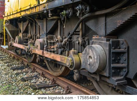 Drive mechanism of an old steam locomotive parked on rusty rails in the Netherlands.