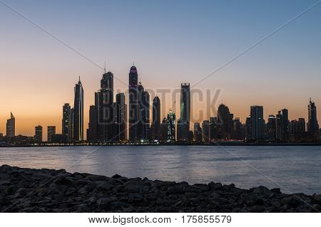 Silhouttes of the Tall Dubai Marina skyscrapers as seen from Palm Jumeirah in UAE.