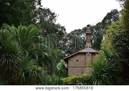old gardener's 1800s brown brick house in botanic gardens with green ferns