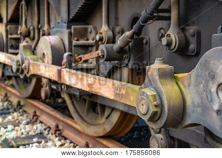 Weathered drive mechanism of an old  diesel-electric locomotive parked on rusty rails in the Netherlands.