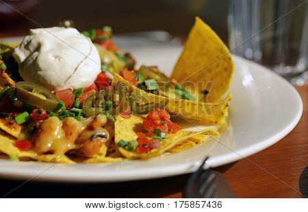 Traditional Mexican food nachos with corn chips, cheese and hot pepper