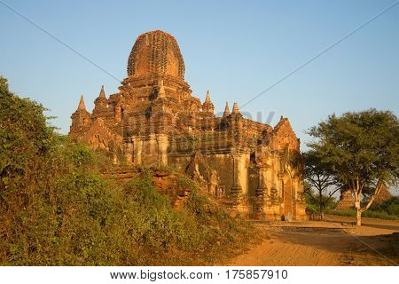 Ancient Buddhist pagoda Tha Kya Pone in rising sun closeup. Old Bagan, Myanmar