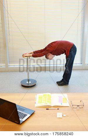 Middle age man doing bending exercises - short break for exercise on pneumatic stool in office