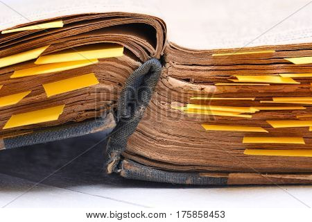 Old open book with paper bookmarks on desk close up