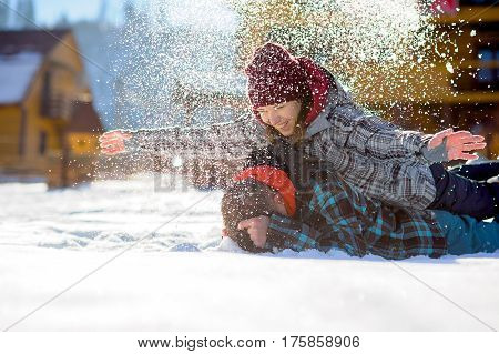 Young couple lies on the snow. The girl climbed onto the back of her boyfriend and sprinkled it with snow. Between them comic fight. Sunny winter day. Good mood. Young people smile