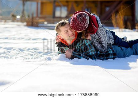 Young couple lies on the snow. Girl climbed onto the back of her boyfriend. She kisses the guy on the cheek. Sunny winter day.