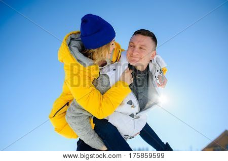 Young man holding his girlfriend on his shoulders. Girl embraces guy for neck. Young people look at each other with love and tenderness. Against the background of the blue sky.
