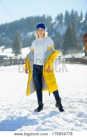 Beautiful young woman in a bright yellow down-padded coat poses for the camera. Serene winter day. Brightly the sun shines. Woman has a great mood. Against the background of a picturesque winter landscape