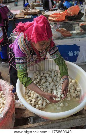 Yuanyang, China - February 21, 2017: Hani Woman Selling Tofu In The Shengcun Local Market In Yuanyan