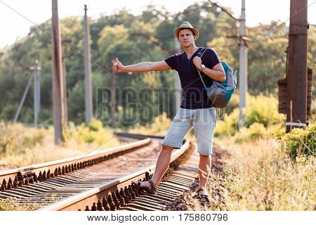 Young Backpacker catching Train showing hitch-hiking Hand Sign on dirty Countryside Railroad with Forest and Sunlight on Background