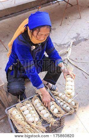 Yuanyang, China - February 21, 2017: Hani Woman Selling Eggs In The Shengcun Local Market In Yuanyan