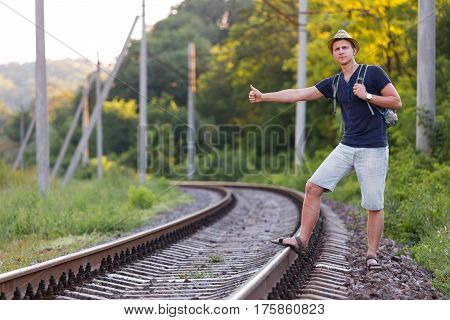 Young Backpacker catching Train showing hitch-hiking Hand Sign on dirty Countryside Railroad with Forest on Background