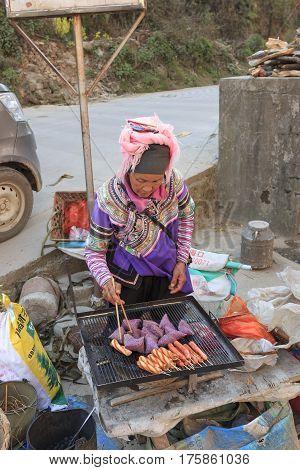 Yuanyang, China - February 21, 2017: Hani Woman Preparing Street Food In The Shengcun Local Market I
