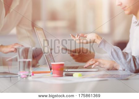 Throw Window View of Casual dressed Man and Woman discussing Business Project at Computer on grey Desk with Color printed Charts Media at Modern open Space Office.