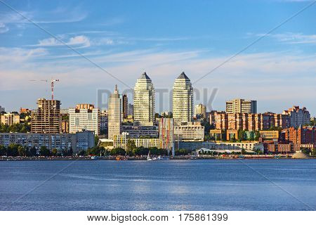 Sunset View city Skyline of small scale east European Town with high Business Buildings and River on foreground