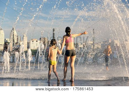 People fleeing from the heat in a city fountain in the centre of a European city during extremely hot summer day when temperature reached 38 degrees Celsius. July 2, 2016, Dnipro, Ukraine