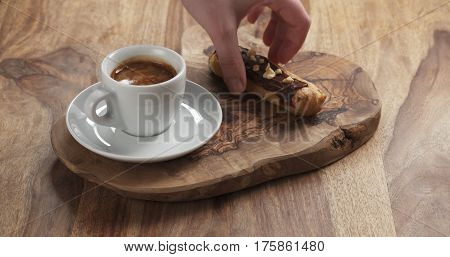 man hand bring espresso and eclair with hazelnuts,