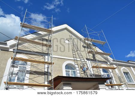 KYIV UKRAINE - March 22 2017: Painting and Plastering Exterior House Scaffolding Wall. Home Facade Insulation Sctucco and Painting Works During Exterior Wall Renovations and Repair. Builder Worker Plastering House Facade Outdoor
