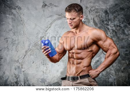 Muscular caucasian man on diet resting after exercise And drinking protein powder from shaker in studio