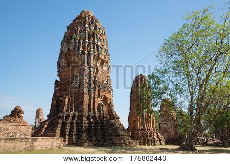 Ruins of ancient prangs of the temple complex Wat Mahathat on a sunny afternoon. Ayutthaya, Thailand