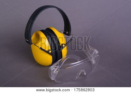 Safety glasses and yellow ear muffs on gray background