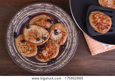 Wholegrain flour fritters bilberry on a plate on a wooden background