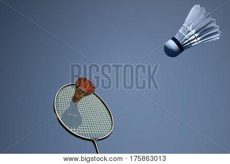 Golden shuttlecock and badminton racket sky blue.