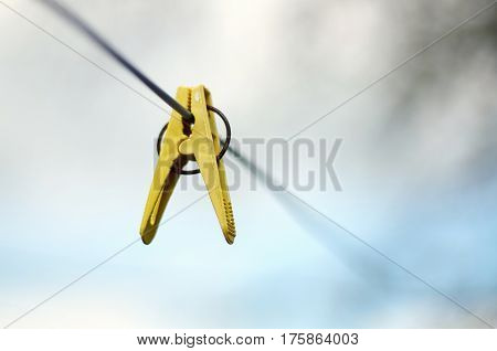 Closeup of Colorful clothes peg on a rope isolated on light background