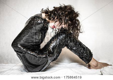 Pretty face woman confined in black foil