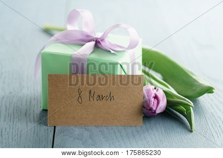 green gift box with purple bow and tulip on blue wood background with 8 march greeting card, romantic photo
