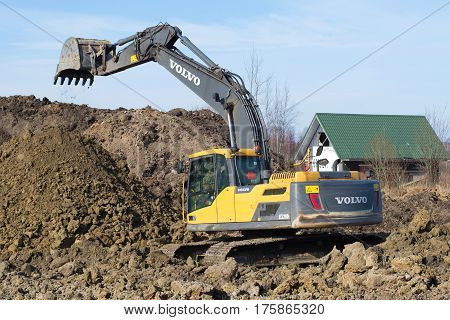 LENINGRAD REGION, RUSSIA - MARCH 09, 2017: Working crawler excavator Volvo EC220Dl closeup, spring day
