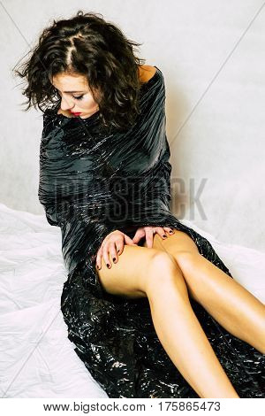 Pretty face melancholy woman confined in black foil