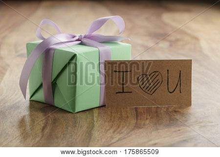 green paper gift box with purple ribbon bow on old wood table with i love you paper card, shallow focus