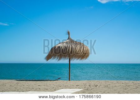 A straw umbrella at the beach with perfect sand and blue sea at Torremolinos (Malaga province Andalusia Spain).