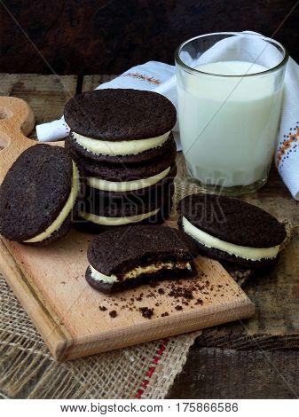 Homemade Oreo Chocolate Cookies With White Marshmallow Cream And Glass Of Milk On Dark Background. S