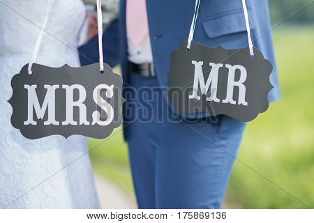 black table with inscriptions in the hands of the groom and bride