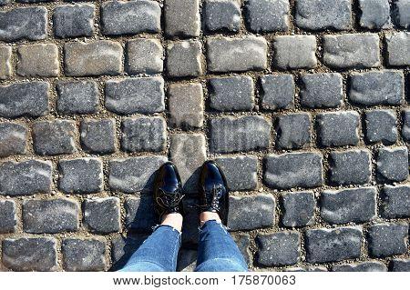 women feet on the stone street.  girl feet