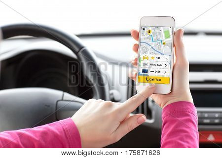 woman hands in car holding phone with app call taxi on screen