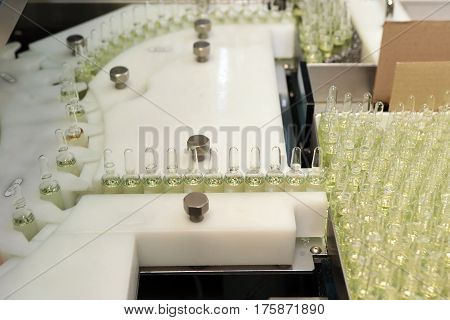 Sterile bottles and ampoules on the dispensing line. Sealed ampoules with medicine.
