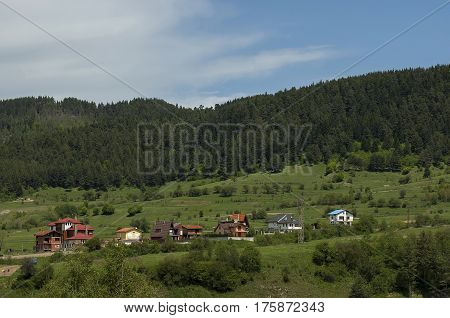 Scene with mountain top, valley and residential district of bulgarian village Beli Iskar, Rila mountain, Bulgaria