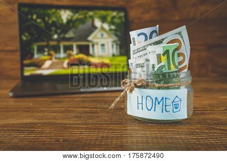 save money in jar for house, image of a house in laptop wooden background