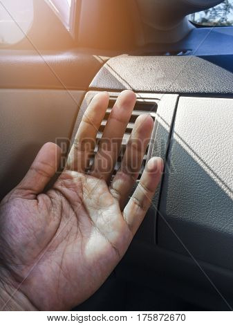 Hand on air conditioner vents car with sunlight.