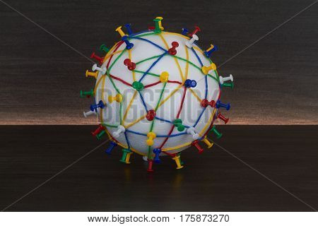 Colorful wool threads on a globe form a network between pins.