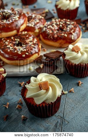 donut rings and vanilla caramel cupcakes with white and dark chocolate chippings and icing served on board.